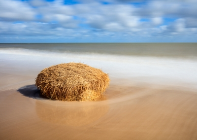 A fallen straw bale on the beach due to coastal erosion at Covehithe on the Suffolk Coast