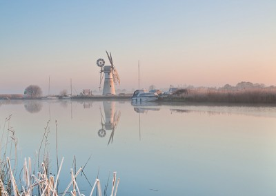 Thurne Mill reflecting in the River Thurne following an overnight winter frost