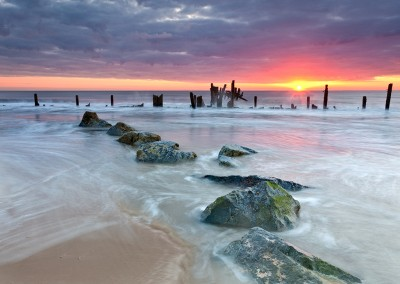 Happisburgh beach and the derelict sea defences captured at sunrise on the Nofolk Coast