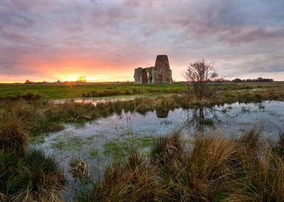 St Benets Abbey at sunset reflecting in medieval fishponds on the Norfolk Broads