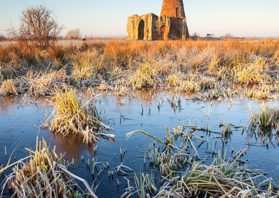 St Benet's Abbey on a frosty morning on the Norfolk Broads. The frozen water in the foreground is from the medieval fish ponds that would have kept the monks well fed.