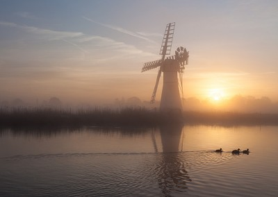 Thurne Mill at sunrise on the River Thurne, Norfolk Broads