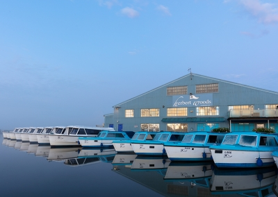 Herbert Woods day boats ready for a busy day on a misty summers morning on the Norfolk Broads