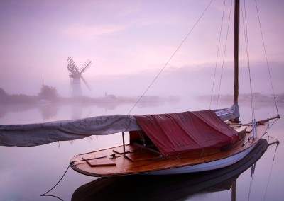 Thurne Mill and sailing boat at dawn on a misty morning on the Norfolk Broads