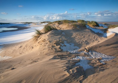 Winter snow on the beach and sand dunes at Holkham Bay on the North Norfolk Coast.