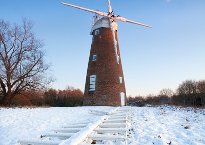 Billingford Windmill in Norfolk captured here in snow with the main sails on the ground undergoing restoration work.