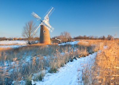 The leaning Hardley Windmill following winter snowfall on the Norfolk Broads