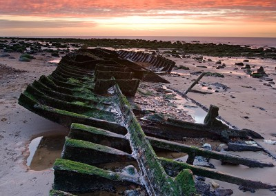 Sunset at old Hunstanton on the North Norfolk Coast. Due to its position on the wash Old Hunstanton is one of the few places on the East Coast where its possible to catch the setting sun over the sea at all times of the year. Here the image shows the shipwreck remains of the Sheraton.