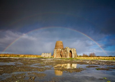 Dramatic hail storm and rainbow captured at the remains of St Benet's Abbey on the Norfolk Broads