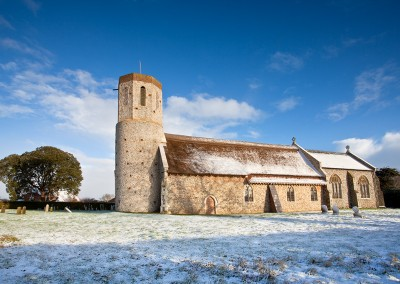 West Somerton traditional Norfolk round towered church following light snowfall on a winters day