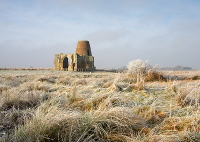 Frozen Marsh land and reeds with St Benet's Abbey in the background on the Norfolk Broads following a winter Hoarfrost