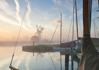 Sailing boat in the mist at dawn on the River Thurne, Norfolk Broads