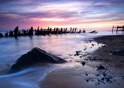 The ruined wooden sea defences and many of the newer rocks which have been placed on Happisburgh beach to help protect against coastal erosion.